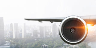 Above above business city. Mixed media. Wing of airplane that flying above modern cityscape. Mixed media Royalty Free Stock Photo