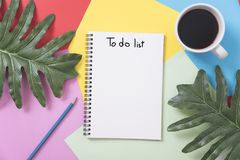 Above blank to do list notebook with leaf and coffee cup. On color design background Stock Image