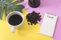Above blank to do list notebook with leaf and coffee cup. On color design background Stock Images