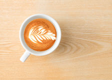Time for espresso. Above capture of white coffee cup with tree shape latte art on wood table at cafe stock photos