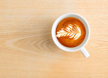 Time for espresso. Above capture of white coffee cup with tree shape latte art on wood table at cafe royalty free stock image