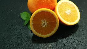Orange with leaf on wet table stock video