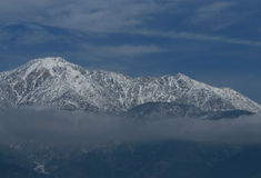 Above the Clouds. Snowy Mt. Baldy from Rancho Cucamonga whose shape is mirrored in the clouds above Royalty Free Stock Image