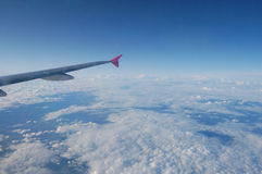 Above the clouds. Aircraft wing flying high above the clouds Stock Photos