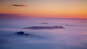 Above the Clouds. Panoramic shot of sunrise showing radiation fog with islands of land appearing Stock Image