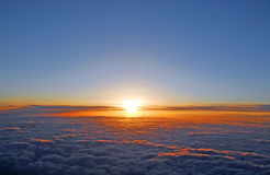 Above the clouds. Spectacular view of a sunset above the clouds from airplane window Stock Photos