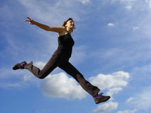 Above the clouds. Young woman jumping high in the air Stock Image