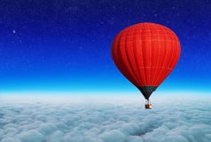 Balloon flies above the clouds. The concept of travel. Above the clouds an air-red balloon flies. The concept of travel stock image
