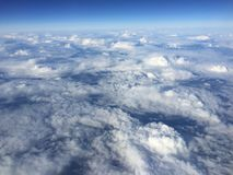 Above the clouds in the blue sky. From the plane royalty free stock photo