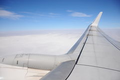 Plane wing flying above the clouds. Flying above the clouds with airplane royalty free stock photos