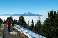 Above the clouds, Mount Rigi, Switzerland. Hikers at Rigi Staffelhoehe, View towards Pilatus and above the Lake of 4 Cantons which is under a thick fog layer Royalty Free Stock Photography
