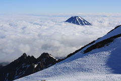 Above the clouds. Mt. Ngauruhoe seen from the crater rim of Mt. Ruapehu new Zealand Royalty Free Stock Photo