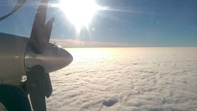 Above clouds. White clouds taken form above while flying in a plane, sun royalty free stock image