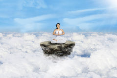 Above clouds yoga in white. Beautiful woman in white doing yoga on the rock above clouds Royalty Free Stock Images