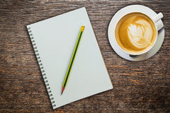 Above coffee and notebook with pencil on wood Stock Images
