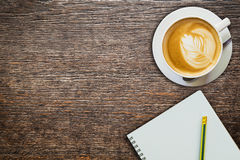Above coffee and notebook with pencil on wood Royalty Free Stock Image