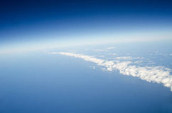 Above the earth at the clouds below Royalty Free Stock Photography