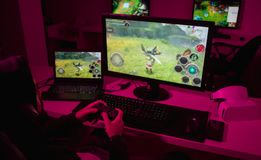 Man playing video game in dark room stock image