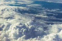 Above heaven concept, view from airplane to fluffy white clouds and blue atmosphere, nature skyline landscape. Toned Royalty Free Stock Image
