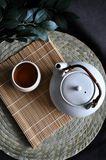 Above of Hot Tea Set on Bamboo Mat. Above of Japanese hot tea set put on bamboo mat with dark gray background royalty free stock photos