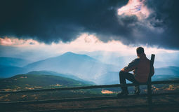 Above the Hoverla. Instagram stylisation. Man sitting on a wooden fence and enjoy rays of sunlight, shining through the clouds to the mountain hills. Carpathian Stock Images