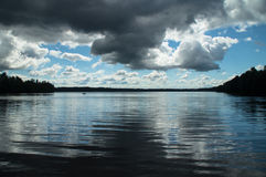 Above the lake clouds gather. Blue sky and white clouds over the lake displaces black thundercloud stock photos