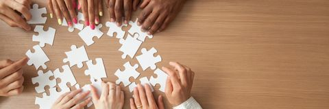 Above panoramic view hands of diverse people assembling jigsaw puzzle royalty free stock images