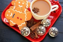 Above photo of three gingerbread men and coffee with star anise. Wooden background with red plate with tree gingerbread men a mug of coffee. Inside the coffee royalty free stock images