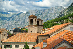Above red roofs of historic town Kotor with towers St Tryphon's Cathedral, Montenegro and scenery clouds on background Stock Images