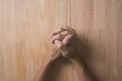Above of religious man crossed hands in prayer on desk. Concept hope, believe Stock Image