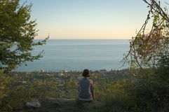 Above a seaside town. At sundown time a woman sits on a rock above a seaside town stock photo