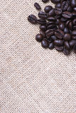 From above shot of coffee beans on tablecloth on wooden table. Vertical shot. Texture Royalty Free Stock Image