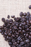 From above shot of coffee beans on tablecloth on wooden table. Vertical shot. Texture Royalty Free Stock Images
