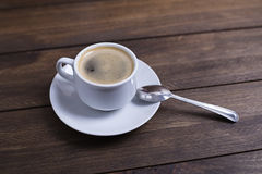 From above shot of cup with tasty coffee standing on wooden table. Royalty Free Stock Photography