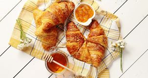 Croissants and condiments composition. From above shot of delectable fresh croissants lying on checkered towel near bowl of yummy jam and jar of sweet honey on stock footage