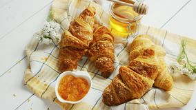 Croissants and condiments composition. From above shot of delectable fresh croissants lying on checkered towel near bowl of yummy jam and jar of sweet honey on stock video footage