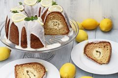 Lemon Bundt Cake with Slices. Above shot of lemon cream cheese bundt cake with cream cheese filling in the center with nearby slices. Extreme shallow depth of stock photography