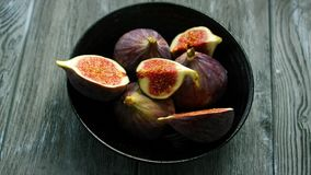 Bowl full of cut figs. From above shot of simple black bowl filled with served cut halves of fresh juicy figs on wooden table stock footage