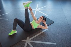 Cheerful adult sportswoman training abs royalty free stock photo