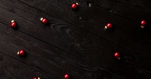 Small Christmas beads on table. From above shot of tiny red Christmas beads lying on surface of dark timber tabletop stock video