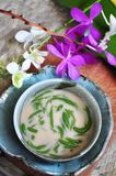 Above shot of Traditional Dessert Cendol. Serve in bowl with orchid decorated on background royalty free stock images