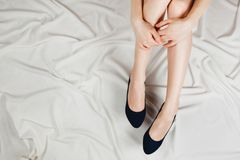 Above shot of white woman`s legs in a high heeled dark blue shoes sitting on bed with white sheets. Royalty Free Stock Photos