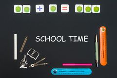 Above stationery supplies and text school time on blackboard. Concept back to school, above stationery supplies and text school time on black backboard Stock Photos