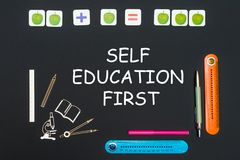 Above stationery supplies and text self education first on blackboard. Concept back to school, above stationery supplies and text self education first on black Stock Photo