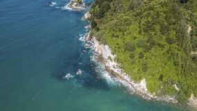 Above steep cliffs with green trees and blue ocean