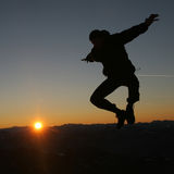 Above the sun. Mans silhouette on sunset sky Stock Photo