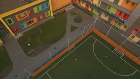 Above top view children play football soccer at school stadium aerial 4K UHD. Footage stock footage