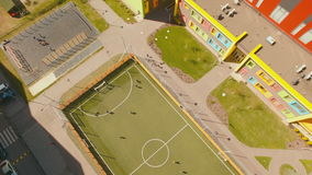 Above top view children play football soccer at school stadium aerial 4K UHD. Footage stock video