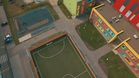 Above top view children play football soccer at school stadium aerial 4K UHD. Footage stock video footage
