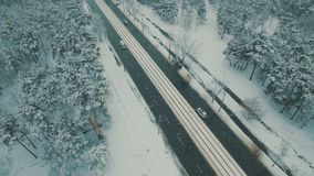 Above top view on winter forest road with cars and tram. Snowfall aerial drone footage. 4K UHD stock video